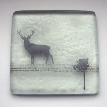 Fused glass tile in a square shape with a black silhouette of a stag on a text strip with graffiti style illustration