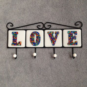 Four hook metal coat rack with four hand cut fused glass tiles spelling the word LOVE