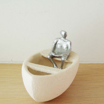 Woman in a boat sculpture, clay and aluminum sculpture of seated figure in a boat, modern sculpture, Greek sculpture