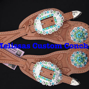 Light oil spur straps. Light Turquoise and Peridot Swarovski crystals. Cart buckles and two 1-1/2 inch shiny silver conchos.