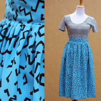 Vtg 80's high waist midi skirt knee length  bold print turquoise black Size 6 lightweight flowy pleated front button side
