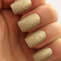 A set of 20 textured, sparkly gold fake nails in 10 different sizes