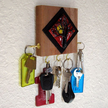 A mini-art plaque featuring a wire tree is mounted on multi layers of wood and adds interest to this compact five hook Key Rack.