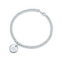 "Tiffany & Co. - Tiffany Notes ""I Love You"" disc charm in sterling silver on a bead bracelet."