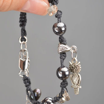 Handmade black woven bracelet made of threads beads and natural stones