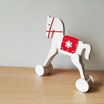 Christmas horse on wheels, white rocking horse retro toy, white horse with red blanket saddle with a snowflake, decorative Xmas horse