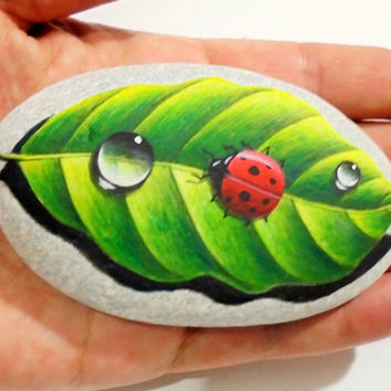 Painted stone ladybug on a leaf !  Is Painted with high quality Acrylic paints and finished with Glossy varnish protection.