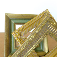 Three small square picture frames in various shades of gold