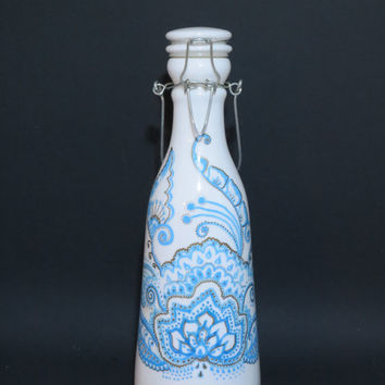Hand painted lotus floral Mehndi design in light blue and gold on ceramic milk bottle