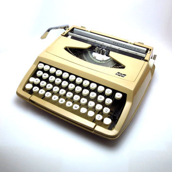 Cream 1960s Smith Corona Portable Typewriter. Made in England. In Mint Condition and Fully Operational. Includes Portable Carry Case.