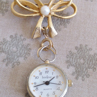 Bonjour Watch on a Lovely Bow Pin with Pearl Center