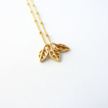 Gold leaf charm necklace on satellite chain | Tiny charm necklace, Dainty jewelry