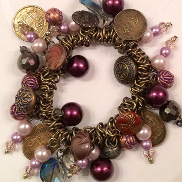Stretch Charm Bracelet comprised of brass religious medals, victorian buttons and crystals.